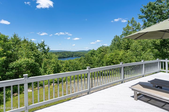 The expansive deck spans the back of the house and is accessed from the porch, great room, and primary suite.