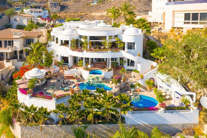 """This luxurious 8,000 square-foot villa is located in the exclusive gated community of Pedregal de Cabo San Lucas. A fabulous cliff-front retreat perched 'Above it All...at the End of the Earth...' Villa Botanica features breathtaking panoramic views of Sea and Sky The interior design is a remarkable blend of neo-classic Greco-Romanesque strength, interconnecting circular rooms of sea-scallop white, oversized hand-tinted red-oxide/umber-toned terracotta, massive tandem columns reach to the 14' ceilings, huge painted domes (7), dramatic curves and winding passages reminiscent of the nautilus seashell or an old-school futuristic sci-fi palace. Sliding glass walls reveal 180unobstructed views of the nearly impossible-to-believe azure blue Pacific, the breaking surf ever-present, soothing and fiery sunsets year-round boil-down center-stage, exquisitely; low-horizon cirrus-nimbus striations render abstract streaks and smears of tangerine, canary, coral-to-indigo,""""a Happy Hour of twilight passion. It's hard to imagine a more perfect views in all of El Pedregal. The whimsy of Villa Viva, it's artful design touches throughout are sure to inspire wonder.... Individually climate-controlled suites, many of them domed, most with one or more king-sized beds; fiber-optic wifi makes media delivery to all rooms personal and easy; full bathrooms and views of the Pacific from every pillow. The gourmet kitchen is in fact a chef's dreams """"Home-style cabinets traded-OUT / beautiful food & cookware display-INcounter-seating for ten surrounds the exhibition-style cooking arena restaurant grade refrig's tucked under the counters of leather-textured stone, Mexican artisan tile, Guadalajara metals and woods; Vulcan French-top range, pot-filler spout above the burners, and at the heart, an open hearth, wood-fired stone oven that heats to 800° in 10 minutes and bakes an authentic Neapolitan pizza or Fajitas al gusto in two! Your office-away-from-the office is provisioned with the latest model M"""