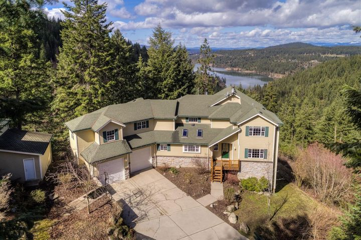 Lake Fernan views from this 50 acres divided into 4 separate parcels, with large custom built home secluded in the trees.