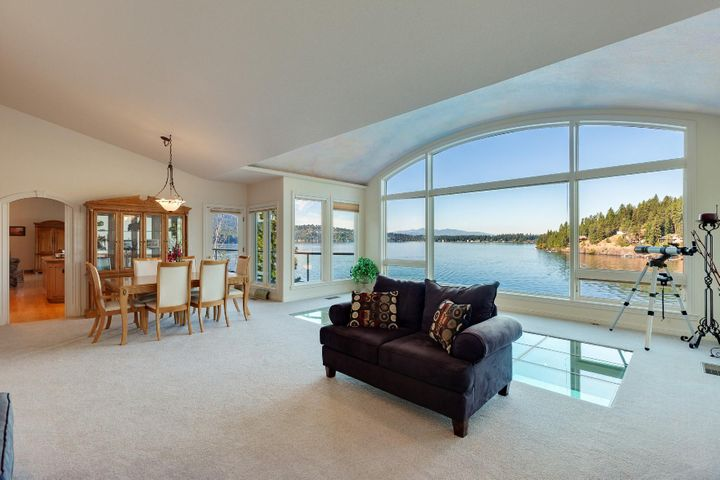 Stunning Hayden Lake waterfront home with mezmorizing lake views, gas fireplace, dining area, and door to deck. Glass floor is always a conversation piece!