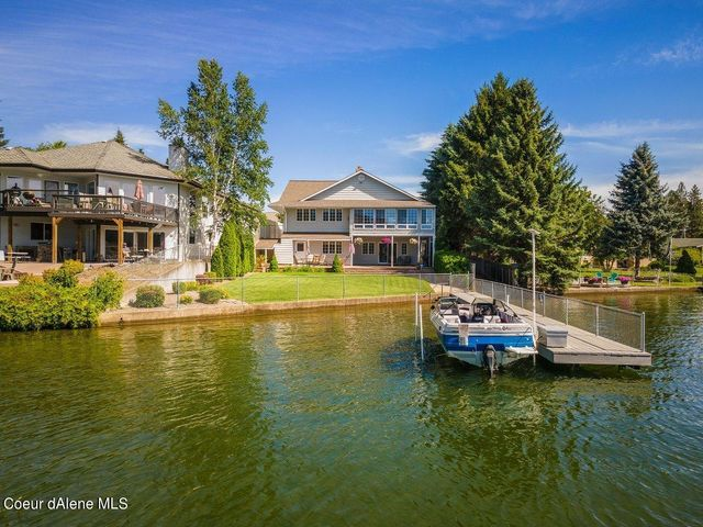 Gentle sloping grass yard to water's edge with a dock and boat lift.