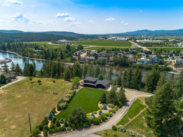 Down a gently winding drive, you will come upon this gorgeous custom cedar home on 2.45 treed acres with 475 feet of Spokane Riverfront. Picnic, swim, fish, and kayak on your own private property. This home is over 2,700 square feet and features hardwood flooring, river views galore from wood wrapped Pella windows. Unique slate and tile throughout this beautiful home, a large master suite with a walk-in shower with a Kohler 9-jet system and a jetted spa tub. Over-sized heated 3-car garage measures 30-40. Kick back and relax on the covered redwood deck overlooking a private, beautifully landscaped yard while the sounds of the river wash your cares away. Eagles, hawks, birds and wildlife abounds. There are too many amenities to list here. A one-of-a-kind immaculate North Idaho Dream Home.