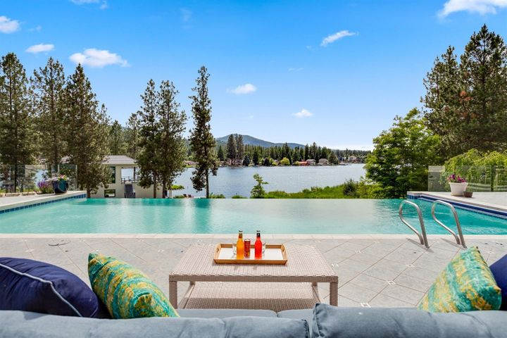 Most Extraordinary and Spectacular contemporary waterfront home in all of North Idaho. Architectural marvel with abundant natural light, 28 foot ceilings with floor to ceiling UV windows and inspiring entertaining spaces from the open great room, pool house cabana with living space, infinity pool, lush park-like grounds, this is the place to relax, unwind, and live life to the fullest. Boasting 8100+SF, 6 Bedrooms, right on the beautiful Spokane River with 200' of private waterfront and your own dock, rare 6 CAR attached garage and an underground storage garage, 5 acres of gated privacy and a privacy conservation inlet view for watching wildlife. More photos at www.ContemporaryWaterfront.com Sunsets beyond compare, savvy and distinctive living for the True Connoisseur of Life