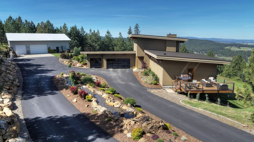 Only 7 minutes to Interstate 90 and situated in the tranquil hills on the Idaho/Washington state line! One of a kind luxury home with unobstructed panoramic views of Post Falls, Spokane Valley, and Spokane. Year round North Idaho living at its finest. Enjoy each of the four seasons comfortably from every room in the house. This quiet retreat features a newly paved road and driveway, energy efficient and green features throughout, Geothermal heat source, private well, and a 36x40 SHOP with 1573 sq.ft. Mother in Law Suite.  Exclusive, luxury living with all the finest amenities this central is hard to find!