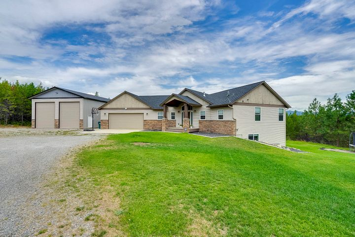 Stunning home on 5+ acres in Double T Estates! The seller spared no expenses updating this impressive home featuring a 30x50 stick built shop with two 16ft roll up doors & full foundation! New carpet & pergo flooring throughout, fresh paint & all new fixtures. The spacious living room has massive windows to take in the views and a cozy rock surround gas fireplace. Bright kitchen featuring granite counter tops and a center island with breakfast bar. The main level master suite offers a private bathroom with a dual sink vanity and tile surround jetted tub. Large family room, 3 bedrooms, a storage room and a full bathroom in the walk-out basement. The large open deck overlooks a true park-like yard w/ a multi level playground, garden area and fire-pit. Why wait for new, this home has it all!