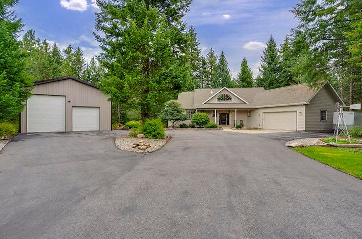 This Beautiful home on 2+ acres nested in the woods offers lots of privacy in desirable Hoyt Ranch. Great location  to  commute from Coeur d Alene and Spokane This Inviting home with lots of windows is nearly 3900  SF with a main floor master suite,  5 bedrooms ( 1 non conforming) 3 full bath, 2 1/2 baths,  tongue and groove ceilings, amazing rock F/P,   hardwood floors, kitchen island. The back deck goes the length of the home.  There is a 30X40 heated shop with circular driveway...nicely landscaped.  Must see.
