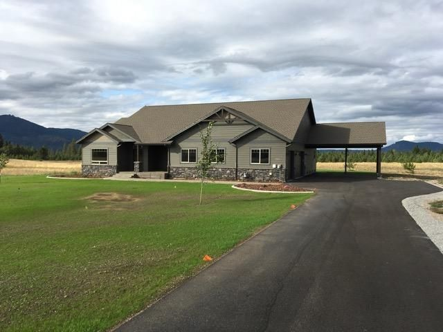 New construction, completed and move in ready, in great close in location, just on the boarder of Hayden and Rathdrum. 5 usable acres, southern exposure and view of surrounding Mountains. Nicely appointed 3 or 4 bedroom 3 bath architecturally designed rancher. Loaded with upgrades some of which are; gas fireplace with custom mantle, granite and tile throughout, top quality appliances, nice comfortable master bedroom suite and hardwood floor. Gas forced air heat and AC. Oversize 3 car garage plus and added 2 car carport. Plenty of room for a shop. Also included is a landscaping package. Easy to show!