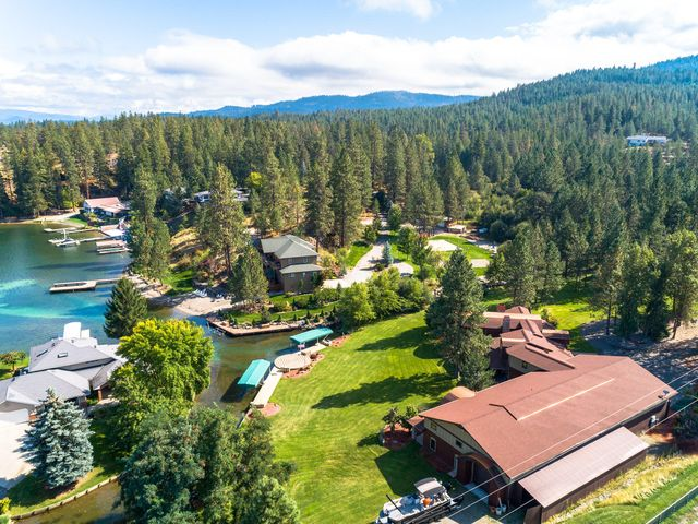 Spokane River Estate Home on Acreage where Luxury, Privacy and Waterfront live in Harmony. Resort-like ''NO WAKE ZONE''Waterfront Perfect for Paddlebording & other Watersports. Enjoy 269' feet of frontage with 3 boat docks for entertainment & fun! Not only do you have a 4700+ sq foot home, but you have an attached 6000+ sq ft climate controlled Shop with a bathroom and bar.This home tastefully boasts 4 bedrooms and 4 bathrooms all en suites with a main floor master. This home has been completelyremodeled leaving no expense spared. The kitchen features all Thermador and Miele appliances, granite and soap stone countertops, 2 dishwashers, mini fridge and an ice maker for your bar entertainment. This home will keep you cozy with the radiant heatfloors on the main floor and extensive