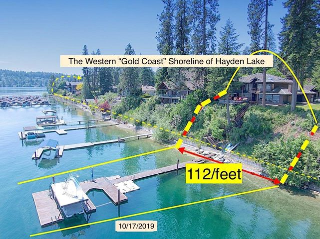 Hayden Lake's Western waterfront the ''Gold Coast''The location is 6-houses north of the iconic Hayden Lake Country Club, a short walk to the Clubhouse's Fairway #1. Both located on one of the finest locations on Hayden Lake.The home is elevated above the water's edge with a 55-foot staircase to a 2-slip boat dock and 112-feet of sandy beach, all with a majestic 180 views of one of Idaho's prettiest lakes.This rural setting is close to town, a 2-mile drive to grocery,  hardware stores, banks, gas stations, restaurants and more.