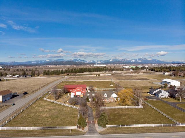 This property has it all! Awesome secured and gated entry farm/ranch setup in Post Falls! This 6,210 SF home with 7 BR/5.5 BA, and 3-car garage is fenced and cross fenced on 4.77 acres with a 40 gpm well!  Home features 3 master suites: 2 main level and 1 second level. The remaining 4 bedrooms are all on the main floor. The master bath includes soaking tub, mounted TV, large walk-in shower, and dual vanities. The kitchen includes SS appliances, granite countertops, glass tile backsplash, and overhead and under counter lighting. The lower level offers flex space living solutions with two family/multi-use spaces and if you are a movie fan, a complete home theater room!  Step outside to your large covered deck entertaining space. Efficient use of property includes two heated shops separated