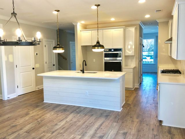 "Shiplap, designer lighting, stainless steel gourmet kitchen appliances, ss hood, gorgeous quartz countertops, lam hardwood floors, 42"" upper white shaker cabinets"