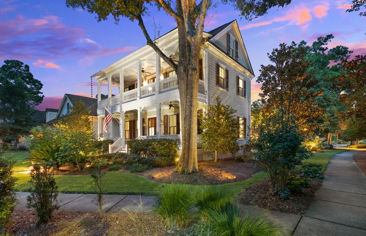 """Fine living is offered in this Lowcountry home that has been immaculately maintained and ready for new owners. It is located in the heart of downtown Summerville offering the ability to walk, bike, golf cart to parks, dining, shopping, and town events held on Hutchinson Square. Convenience to Azalea Square or Nexton, even the interstate, are right around the corner. The front of the home features classical architecture of full front double porches surrounded by meticulously manicured gardens featuring Sago Palms, live oak, and magnolia trees. Enjoy the privacy offered by the mature landscaping surrounding the home and only a neighboring house to one side. The exterior has just been freshly painted to include the shutters which are fully operable with iron hinges and hardware to secure. The gutter system has copper decorative rain chains on the corners of home which add to the charm and customization. Upon entering the glass paneled mahogany double front doors your eye will be drawn to the heavy moldings to include 7"""" colonial style baseboards, wainscoting in the Dining Room, trim around the window, and 4-piece crown molding accenting the 11' ceilings throughout the first floor.  Heart pine 5"""" plank floors and interior plantation shutters are other features to note.  The gourmet kitchen offers granite countertops with an extended bar area, gas cooktop, and stainless steel Kitchen Aid appliances. Downstairs has a guest bedroom suite with full bath, formal dining room, butlers pantry, walk-in kitchen pantry, large great room with built in bookcases surrounding the gas fireplace. The kitchen/great room is lined by 4 sets of french doors and a bank of windows leading out onto the screened porch and patio. The outdoor kitchen under the white pergola conveys to the new owner and features a gas grill and refrigerator for easy entertaining. The stone fire pit is another lounging area and is completed with an iron fence and backdrop of mature landscaping giving maximum privac"""