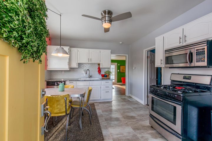 Enter into the updated kitchen with white cabinets, tile backsplash and updated hardware.
