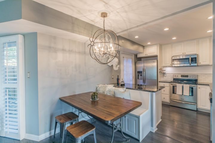 Updated kitchen with raised panel, white, soft-close cabinets and drawers, granite counters, marble backsplash, tons of recessed lights, under cabinet lighting, wood laminate flooring & SS appliances.
