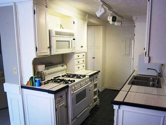 White cabinets, tile floors, tile counters