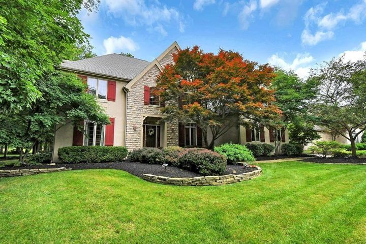 Stunning view of the front of home with outstanding curb appeal with colorful mature landscaping.