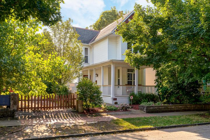 Charming home w/ inviting, wrap around front porch in desirable Harrison West. Tastefully updated throughout  & offering an abundance of natural light. Upstairs you will find 2 generous sized bedrooms, recently remodeled full bath & access to loft area which offers additional space perfect for an office area, storage or more (loft area not included in sq ft). The entry level has a family room w/ built-in shelving & vent-less fireplace, a dining room area, kitchen, additional full bath & laundry area w/ access to the cellar/basement area. You will love relaxing in the fenced-in backyard which boasts a paver patio & grass. Oversized 2 car garage is extra deep & can fit more than 2 cars or be used for storage or a workshop. Convenient location near Olentangy trail, downtown, High St & OSU.