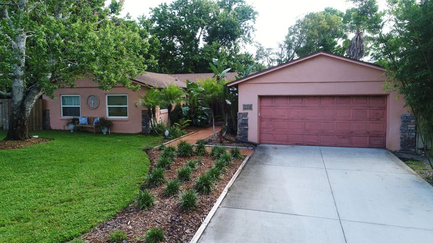 Gorgeous front exterior with beautiful landscaping, extra long driveway and has a southern exposure