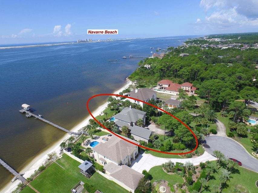 Spectacular Traditional 2-Story Pool/Hot Tub Home with breathtaking views of Santa Rosa Sound and Navarre Beach. The twenty foot high foyer with custom artwork and leaded glass inlays are only surpassed by the elegant Oak wood trimmed spiral staircase. Exquisite Custom Cabinets and Trim with Travertine tile are featured along with rare Coffered Ceilings in  Library and Dining room, make this a very distinctive residence. The huge luxuriously elegant Mas/Bath will take your breath away. The Kitchen features custom hand made cabinets/granite tops, GE Monogram Designer Series appliances, Butler's gallery with wine cooler, rack and ice maker. Media Room,4 large bedrooms,2 baths,balcony overlooking pool on 2nd flr! 3 car gar with build out space for moth-in-law ste! Lush landscaping with palms!