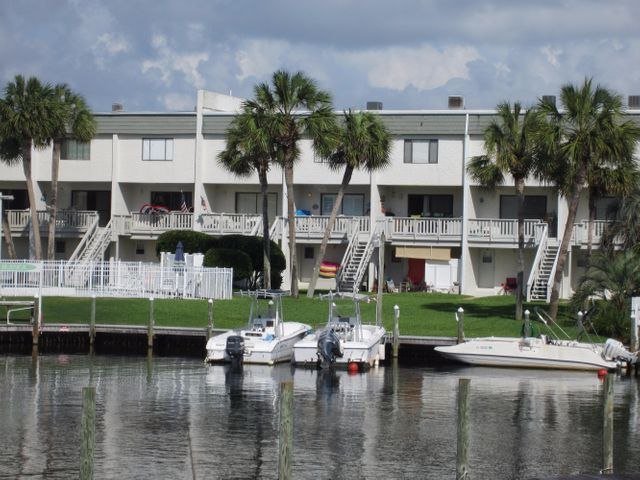 View across canal of boat docks, pool, court yard and boat slips