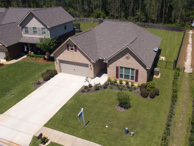 Beautifully landscaped home with expansive driveway.