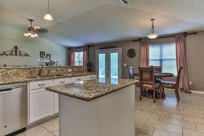 Granite island and counters . Open breakfast area encouraging conversations. Large family room with bamboo and porcelain flooring. Shows beautifully