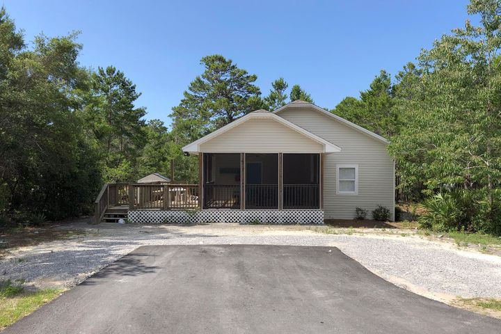 Awesome 2BR/2BA, 1,131SF Home just a short drive to the beach & shops at Gulf Place.  Enjoy relaxing on this peaceful .25 Acre lot away from the noise of 30A.  This home is tucked away in the woods, secluded but only a few minutes from the beach & shopping.  You enter the home through a large screened deck area and into the kitchen.  The kitchen features stainless appliances & plenty of cabinet space.  Off the kitchen is a hall bath, full bedroom, laundry room, & living room.  The living room is large with access to the backyard.  The master bedroom features a private bath and a large walk-in closet, currently being unitized as a bunk room.  Other features laminate floors in the living space & tile floors in the bedrooms.  See yah at the beach!  Blue Gulf was recently paved with drainage.