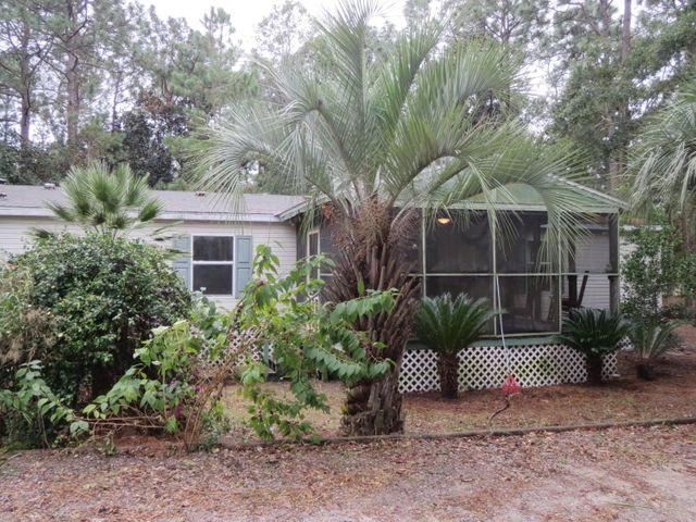 PRICE REDUCTION!  Motivated seller with owner financing available!! So close to the bay and beach that you can walk or ride your bike... just 1/4 mile to the bay and 3.5 miles to Grayton Beach!! This 3 bedroom home on 1/2 acre is nestled among shady trees and feels very private although it's close to shopping, restaurants, and beaches. It has new vinyl plank flooring, updated bathrooms, new appliances, tons of storage, and has been well maintained. There is a separate efficiency apartment (generating $800/mo rental income) and 400 sq ft workshop. Enjoy relaxing and entertaining on the huge screened porch (17x11) and deck (27x10). Includes 2 chicken coops, fruit and nut trees. Refrigerator, stove, dishwasher, washer and dryer convey. AC is 5 years old.
