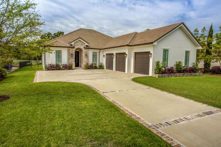 OFFERED BELOW RECENT APPRAISAL! Beautifully constructed, nearly new home with lots of extras in a quiet Regatta Bay neighborhood! This 4-bedroom, 3-bath home includes a large screened patio, pool, and fully fenced back yard on the golf course. Perfect for a growing family or empty nesters who want the convenience of one story!The main rooms feature crisp white walls with wainscoting, wire-brushed 3/4'' red mahogany floors, box tray ceilings, and fabulous Old Chicago brick accent walls in the foyer and formal dining room, with matching brick on the kitchen island and wood-burning fireplace. The large living area opens to both the dining room and out to the patio, all ideal spots for entertaining, whether it's a formal dinner party or poolside barbeque. Family time is likely to be enjoyed. ...in the large open kitchen/family room, which includes beautiful granite countertops, abundant Shaker-style cabinetry with lots of room for storage, a large breakfast bar, and stainless appliances: Frigidaire Gallery Series range with vent hood, double convection oven, and more.   The master suite includes patio access, golf course views, dual vanities/sinks, a soaking tub, separate shower, and separate water closet. Three additional bedrooms are perfect for kids, guests, or a home office, project room, etc.  Enjoy indoor/outdoor living with a large fully screened lanai, with areas in both sun and shade. The fabulous pool includes water features and LED multi-color lighting. The large backyard is fully fenced--perfect for pets and young children--and includes a built-in playground, as well as plenty of space for lawn sports. The extended 3-car garage will easily accommodate a workshop or plenty of recreational equipment.  The home's exterior is finished with smooth white stucco and a ceramic tile roof, which has a 30-year warranty. Construction details include a CMU block foundation, 2x6 exterior walls, R13 & R30 open-cell foam insulation, engineered roof trusses, and Jeldwin viny