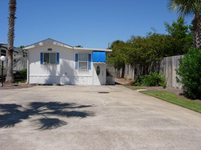 LOCATION, LOCATION, LOCATION. Only 1 block from the beach. This manufactured home makes a great primary residence or rental property. There are no rental restrictions, this would be a great investment. This is a great neighborhood with well kept lawns and clubhouse with a pool. Great location in the subdivision near the rear and on a corner lot for lots of privacy.This the only lot that has 3 parking spaces. Enjoy the screened in patio right in the corner. There is also a 10 x 10 storage room with A/C that some in the area have converted to a guest room. The home has been completely painted and new carpet. Hurricane shutters are in place but can be easily removed after the season. Don't miss this great opportunity be live with-in walking distance to the Gulf's beautiful white sandy beach