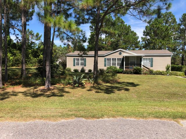 AWESOME LOCATION !!  South of Hwy 98 and only 1.2 miles to Gulf Place and Beach Access at Ed Walline Park.  This well kept home is also located in quiet neighborhood and in a serene setting with views of a lake in the backyard.  Has open living/dining and kitchen areas and split floorpan with master bedroom suite on one side of the home and 2 bedrooms and another full bath on the opposite side of living area.  Large lot to enjoy the outdoors from large back deck.  Roof is only 2 years new !