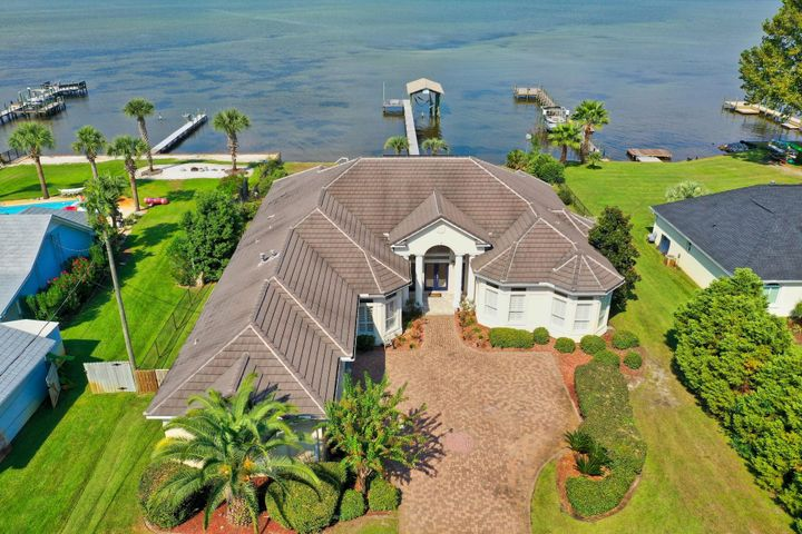 Enjoy coastal living in a serene tropical setting with this Bay front estate in Miramar Beach! This home is on an expansive and private lot boasting over 1/2 an acre.  With 100 ft of water frontage on the Bay, you have your own private oasis! Home is complete with dock, boathouse with slip, sun deck, incredible screened-in pool and covered lanai. Outdoor features a huge back yard with tropical landscaping setting this home apart from the rest. *Check out the lifestyle video and virtual tour of this amazing property in the Photos section.* Ideally the home is one level with beautiful architectural details like trayed ceilings, stunning archways, crown molding & lots of windows offering great natural light and panoramic views of the Bay. The interior has been repainted for a fresh look along with new chandeliers, new hardwood flooring and updated kitchen & baths with Quartz countertops. Kitchen also includes new stainless steel appliances including a double oven and smooth top range, new custom tiled mosaic backsplash, and freshly painted kitchen cabinets. There is a wet bar nearby with a wine fridge, sink and extra storage as well as a generously sized walk-in pantry. The full bath for guests is stunning with newly tiled shower with glass door and Quartz counters. There is also a half bath near the kitchen which is easy access while entertaining. There are 4 bedrooms including a Bay front master, an additional flex room and 3-car garage. The beautiful master bedroom features a tray ceiling, several windows allowing views of the Bay from just about every angle, wood flooring, a master closet with built-ins and an en-suite bathroom. You will feel like you are at the spa in the master bath with Jacuzzi tub, double vanities newly appointed with Quartz and walk-in tiled shower with glass block entrance and recessed lighting. The split bedroom floor plan allows the master bedroom extra privacy away from the other three guest bedrooms. All three guest bedrooms are generous in size and feature crown molding and plantation shutters. There is a great flex room located at the front of the home east of the foyer that would make a terrific office.   The large, covered lanai is the perfect spot to relax and can be accessed from several rooms in the house including living area, dining nook, great room and master bedroom. The screened-in pool area with paver sun deck is ideal for tanning then cooling off with a refreshing swim. The covered porch was freshly painted and offers a fantastic swing to lounge in while taking in breathtaking views of the Bay. Incredible opportunity to own such a prime location with over half an acre of direct Bay front, and just 5 minutes from the pristine beaches along the emerald green waters of the Gulf of Mexico! You can easily access the beach by golf cart across Holiday Road and are also near many dining, shopping and entertainment options. This is an amazing opportunity for coastal living!