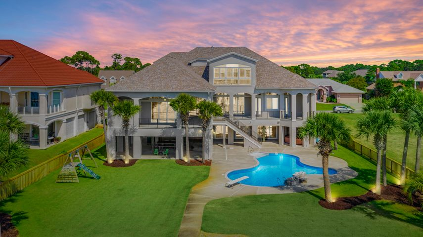 "This regal Sound front home resides on the most desirable street in the golf course community of Tiger Point. Upon arrival, you'll note the grand entryway and beautiful landscaping. The open spacious floor plan encourages entertaining with cascading sliding glass doors, opening up to spectacular Sound views onto the covered balcony. You'll also enjoy the oversized dining room, wet bar and pool room while having guests. The kitchen comes fully equipped with two islands, sub-zero fridge, double wall oven, bread warmer and prep sink. The master suite offers sound views, over-sized his & hers walk-in closets and dressing area. Into the master bath with double vanities, soaking tub with a massive shower with 3 shower heads, water closet with a bidet. On the opposite side of the main living flo This regal Sound front home resides on the most desirable street in the golf course community of Tiger Point. Upon arrival, you'll note the grand entryway and beautiful landscaping. The open spacious floor plan encourages entertaining with cascading sliding glass doors, opening up to spectacular Sound views onto the covered balcony. You'll also enjoy the over-sized dining room, wet bar and pool room while having guests. The kitchen comes fully equipped with two islands, sub-zero fridge, double wall oven, bread warmer and prep sink. The master suite offers sound views, over-sized his & hers walk-in closets and dressing area. Into the master bath with double vanities, soaking tub with a massive shower with 3 shower heads, water closet with a bidet. On the opposite side of the main living floor, you'll find 2 additional bedrooms and 3 full baths and laundry room. The third floor holds a media room with a projection screen (Epson Powerlite Pro Camera), kitchen and bedroom with a full bathroom. The office, just off the media room offers amazing floor to ceiling sound views! Enjoy the convenient elevator to the main living floor, for all your needs. Important notables: brand new within 2 years: New roof, 4 new HVAC units, new pool liner, whole house painted inside and out (exterior with 25 year warranty). SMART HOME with a ""Control 4 System"" which controls the 6 exterior cameras, all home access, sound on all 3 levels, lights, climate control, sprinkler system and fireplace. 2 new exterior staircases with aluminum railing, 2 dehumidifiers on the ground level and 1 in the master bathroom, spray foam insulation in attic and ground floor walls and ceiling, new plumbing and electrical to dock, 2 boat lifts and 1 jet ski lift, landscaping lighting and all new LED recessed lighting. Enjoy panoramic Sound sunsets while lounging in your salt water pool after an epic day boating! Check out our full video tour on the MLS and YouTube."