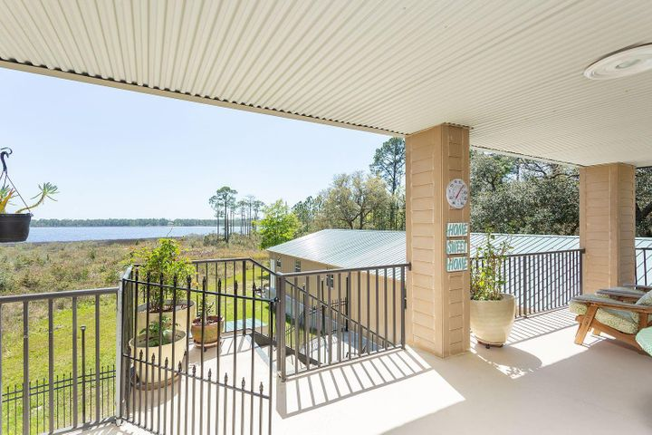 You'll enjoy amazing sunset views overlooking the water from several sitting areas on the grounds. The three-car garage 2000+sq ft of space and a bonus workshop in the back is perfect place for a man cave, she-shed or a game room for your children. Designed with a special area for parking your Boat and RV for convenience. Huge open heated and cooled warehouse/office space located in the main living area along with bonus/office spaces that are individually climate controlled. Two separate living spaces on the first and second floor with each floor including a complete: kitchen, laundry, bedroom, bathroom and living rooms. The layout and design provide endless opportunities for work and play in this private residence, office and warehouse. Enjoy the quiet, the view and safe environment of this spacious property with room indoors and out for any pursuit you can envision. Two buildings on waterfront with direct boat access to the Gulf. Million Dollar Views and 5000 sq. feet on the Water, add a pool, pier and boat dock. Two complete & separate living spaces upstairs & down. Awesome NEW screened Porch overlooking water. Entertain your guest on the spacious upstairs porch and 2 downstairs patios. Game room now in place with Poker Table, Dynamo Billiard Table, you could even add a second story to the inside main building or add an indoor basketball court or seriously even a bowling alley. Major Highway Frontage: NEW 4-lane HWY 87 only 14 miles North to I-10 or 5 minutes South to Navarre Beach. Also INCOME producing vacation rental property on airbnb.