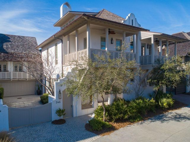 Forwardly designed and masterfully constructed, this quintessential home is nestled within one of the most iconic corners of Rosemary Beach. An elegant architectural wonder positioned steps away from the sugar white sand of the coast and the sea blue green of the Gulf of Mexico, 346 W Water Street enjoys its flow from interior living to the  spacious courtyard.  The home inspires through masterfully crafted details including Venetian plaster walls, pecky cypress columns and beams, masterful Groin Vault ceilings and oversized windows.  The interior and exterior fireplaces provide exceptional gathering spaces to contemplate the day ahead or unwind from a day at the beach. As one enters through the arched hand-carved teak front door, the crisply designed living space welcomes! And moves eloquently into the transitional dining space. Beyond the dining area is the progressively designed kitchen, equipped with a custom Viking range and Quartzite kitchen counters. The main level of the home also features a spacious laundry room and butler's pantry, and a full bath leading to the pool and courtyard.  Walking up the sun drenched stairway with burnished brass balusters, the second floor welcomes with a naturally lit living space, Gulf view balcony, and four of the five bedrooms. An elevator is available to transport between the first and second floors. The third story of this elegant home provides the fifth private bedroom suite, a media room, and a second laundry area.  Adding to the convenience and accommodation of this stately home, across the charming courtyard resides a freshly renovated carriage home equipped with a full kitchen, charming living space, sleeping loft and tastefully updated decor.  The heart of this beach retreat can be found in the oversized courtyard, featuring a full Dacor summer kitchen and plunge pool with water feature. Build a lifetime of memories by the outdoor fireplace, and enjoy the unique beach lifestyle of this extraordinary Rosemary Beach ho