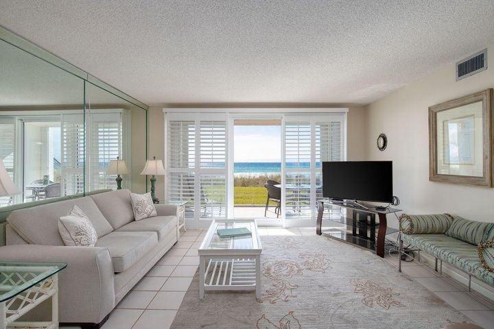 """Sold fully furnished, you can move right into this beachfront condo and start enjoying the lifestyle and incredible Gulf views it has to offer. Step straight out from your first floor patio onto the nearby beach for morning walks with seabirds and passing dolphins. Return home invigorated and ready for breakfast on the terrace within sight and sound of those white-edged emerald waves. The property is beautifully light and bright, thanks to full-width patio doors and windows screened by plantation shutters. The sitting/dining room has durable tile floors and comfortable furnishings in light beige tones. In contrast, the spacious open-plan kitchen has pristine white appliances and light wood cabinetry. The master bedroom shares those endless beach, dune and Gulf views from the moment you wake up and throw open the shutters. The guest bedroom offers a wall of mirrors, creating a bright modern space. Two full bathrooms round off the accommodation. In addition, the condo features an outdoor storage closet for beach chairs, bikes and other outdoor essentials, as well as a full size washer and dryer.   Located in the gated condo community at Grand Mariner, this Gulf-front property has 375 feet of beach with soft white sand for sinking your toes into. The condo has restricted rental rules with minimum 90-day rentals to preserve the privacy and peace of this well-maintained community. Living in Grand Mariner opens the door to all the shopping, dining and cultural attractions that Destin has to offer five minutes away. Go fishing in the """"world's luckiest fishing village"""", enjoy the freshest catch of the day around Destin Harbor, or chill out on your private terrace drinking in those entrancing Gulf views"""