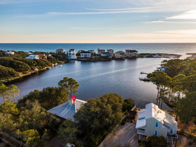 This charming 30A beach cottage boasts the opportunity to experience living on a rare coastal dune lake with panoramic views nestled amidst south walton's local wildlife. With 110 ft. of lakefront property sculpted with oaks, flowering trees and shrubs, it's easy to see why this home provides an ideal setting for canoeing, kayaking, paddleboarding, fishing and swimming with direct beach access. Throughout the home, you'll find light-filled rooms, high ceilings providing an open and spacious feel, and expansive lake and Gulf views. The home's living space provides a fireplace along with a screened porch for entertaining outdoors or enjoying incredible Florida sunsets. This special 30A property is a mere five minute drive (or less) to Butler Elementary, Santa Rosa Golf and Beach Club, Ascension Sacred Heart Hospital as well as boutiques and restaurants in Grand Boulevard.
