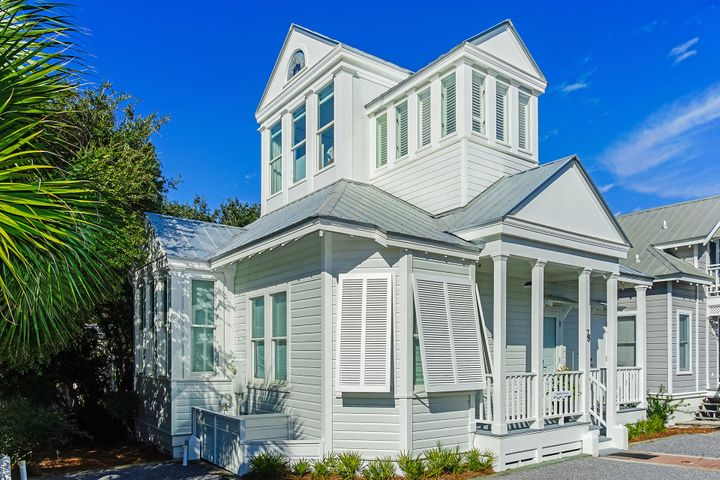 Located along 30A in Seaside, FL, this iconic 2-bedroom + Loft, 2 bath beach cottage offers over 1,100 square feet in prime position in Rosewalk, mere steps from the Tupelo Pavilion private beach access.  Completely remodeled in 2019, with modern features, this white beach cottage offers quintessential original charm with soaring vaulted ceilings and windows. Originally designed by Robert Orr and Melanie Taylor. Upon entrance to the cottage, the warmth of the hardwood floors envelops you against the coolness of the white walls and high ceilings. Perfect for intimate dinners or family gatherings, the living area and elegant dining area are adjacent to the professional kitchen any chef will appreciate, complete with sleek modern custom cabinetry and high-end and European appliances. Escape upstairs and watch the blue Gulf views and the sunset, from your own private Master Bedroom, featuring an ensuite Master bathroom with high vaulted ceilings, surrounded by windows, and a small private balcony facing the magnolia trees and sunsets. There is a queen bedroom with a daybed on the first floor and a cozy loft with a twin bed on a second floor. Both rooms share a full bath with a tub in the main hall, where you can also find your Bose stackable washer/dryers. No detail has been spared including two new A/C with UV light system.   Notable features of the home include: stackable Bose washer/dryer, outdoor shower, gas BBQ grill, and a beautiful front porch facing nature, perfect for lounging and entertaining. This chic house is completely furnished and is ready for beautiful memories and to be featured in a coastal magazine. The house's main entrance and porch faces a garden footpath and has an additional street-side entrance with two parking spaces for your convenience. Walk to restaurants and to unique shops in a pedestrian paradise.