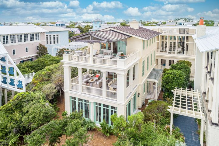"""This exclusive residence has been the cover story for several publications including Architectural Digest, Coastal Living, The Coastal Cottage, 30A Style and more. Featured on Oprah.com as one of the 7 Prettiest Summer Porches (2017). ''Everything about this privately owned cottage emotes a singular impression...Style. There are front porches on all three levels with the view more encompassing than the one below. These amazing views of the gulf compliment the generous living spaces and four bedrooms, three on the first floor and the master suite on the third level. The first floor's expansive porch features two sumptuous bed swings with plenty of seating to relax and listen to the gulf breezes.  On the second floor the house opens up and outward from the kitchen, dining and living areas in grand sequential order. Views of the Gulf take center stage without a doubt. The distinctions between indoors and outdoors merge and lines of the architecture melt away.  The third floor is devoted to the stunning master suite, with a deliberately open and out-there with nature design.  On the porch, an articulated truss offers shading and justification of the home's piece de resistance, the single Ionic column. This home reflects all the touches and traditions of coastal life with the best of attention given to every detail. Narnia's obvious bravado is neither daunting nor imposing. It is engaging and inviting thanks to its comfortable scale, exacting proportions and a romantic marriage of vernacular coastal architecture and 1930's Swedish Classicism.""""  Coquina stone pavers surround the exterior first level and also used as flooring inside the foyer hall. The entire home is handcrafted of wood like a piece of fine furniture. Reclaimed wide plank pine flooring was used in the living areas and master suite.  Coffered bead-board ceilings, board-and-batten and nearly 100 different custom made moldings can be found throughout the house. Additional amenities include elevator, fireplace"""