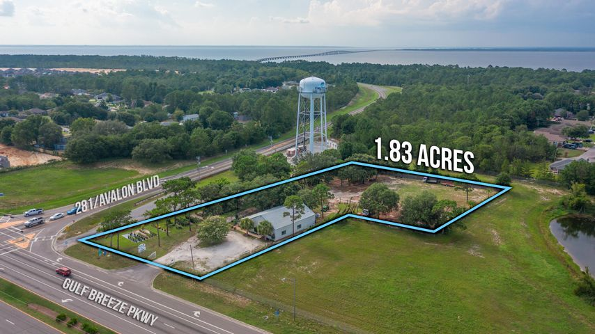 EXPANSION OPPORTUNITY / INCOME PRODUCING.  SELLER WILL FINANCE; BUSINESS MAY CONVEY ALSO.  This underdeveloped piece, which could effectively become a corner parcel, is located directly in the heart of the exploding Gulf Breeze area.  As expansion & density from all sides increases, this cornerstone commercial parcel places one in a high traffic, high visibility location, directly across from national brands such as Wal-Mart and Lowe's, among others.  Excellent opportunity for a buy-out by an existing landscaping / garden related company who desires to expand and capture market share; or redevelop to highest and best use.  Metal building & roof; NEW WINDOWS; open retail space and several office spaces on first floor, & second floor. *Partial ground lease on rear of prop @ $1500/mo Would be highly profitable to ground lease the rear portion of acreage and operate business or lease the retail storefront.  Existing business operation may or may not convey at Buyer request. DON'T MISS THIS OPPORTUNITY.  Seller may finance with terms.