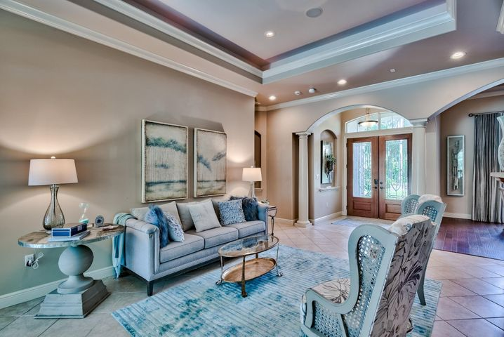 Inviting entrance steps into the parlor with 13' coffered ceiling, firplace that overlooks the covered lanai & Pool.