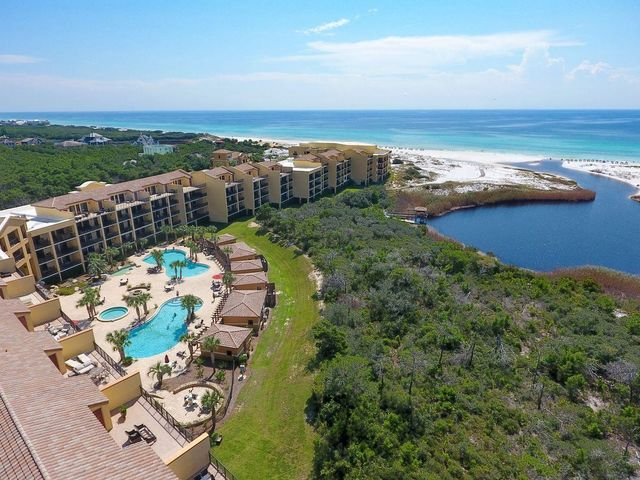 Overlooking the pristine vistas of Western Lake and the Gulf of Mexico, this two-story condominium is the pinnacle of luxury. In addition to having five bedrooms, five full baths, and an in-home theater/media room, this 4,511 sq/ft unit is replete with high end finishes and complemented by nearly 700 square feet of outdoor living space. The whole unit boasts travertine flooring and 10' ceiling height throughout. The open floor plan of the first level provides a spacious and versatile space for entertaining. The incredible kitchen comes with custom made cabinetry, stainless steel Viking appliances including a sizable gas range, and high end granite countertops. The first floor also offers two bedrooms with ensuite baths, a custom built-in wet bar, and an oversized balcony that sits at 27 feet in elevation to maximize the incredible sunset views this unit captures. The master suite is a masterpiece of elegance and occupies most of the second floor. It boasts a spacious private balcony with panoramic views, a whirlpool tub, and a spacious walk-in closet. Also on the second floor is the in-home theater which is a superb addition to the space and provides an extra level of comfort and relaxation. This property is being offered fully furnished and turn-key.  Sanctuary By The Sea is an exclusive gated community located on the West end of Scenic Highway 30A and it boasts incredible amenities including 650' of private beach frontage, 23 acres of privately owned land bordering a nature reserve, fitness facilities, three swimming pools with pool-side Cabanas, waterfalls, community fire pits, Viking BBQ grills, a Gulf-front owner's lounge, virtual golf simulator, and an arcade. Sanctuary By The Sea is centrally located near world class shopping, dining, and entertainment experiences in renowned locations such as Grayton Beach, Watercolor, and Seaside.