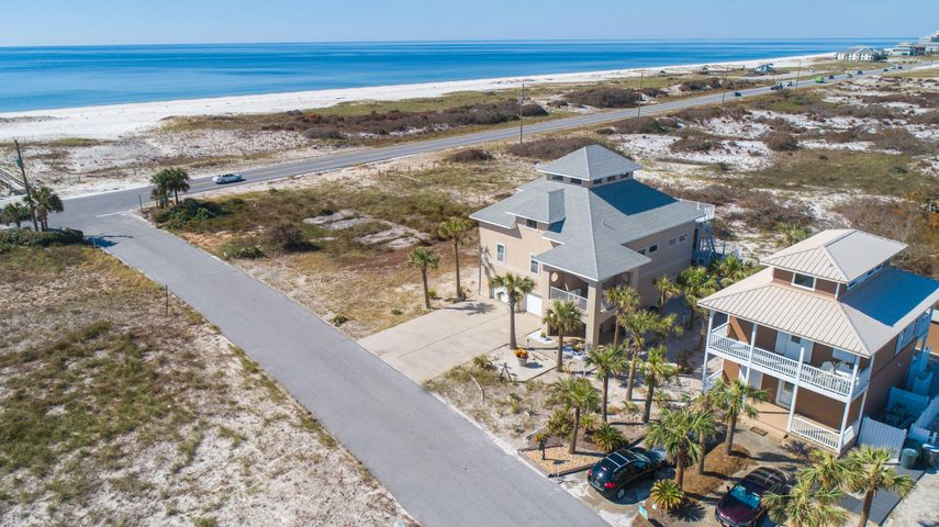 With magnificent Gulf views nestled on Perdido Key, this fortress is built with ICF (Insulated Concrete From) construction, steel framework and concrete pilings, 3 levels of poured concrete floors and an elevator to the second level. You'll enjoy the public beach access directly across the street and countless sunsets and views of Ol' River from the sunroom and top sundeck on the 4th floor with protected views of Perdido Key State Park. The sunroom is encompassed with cork walls and all windows open to enjoy the open air. The spacious living area has vaulted ceilings which flows into the dining area and kitchen. The kitchen comes equipped with granite counter tops, island and ample cabinet storage. The spacious master suite has Gulf views from the bed and comes equipped with an oversized w alk-in closet, sitting area/gym/office space and the master bath has a large jetted tub with heater, encompassed with granite, double granite vanity and separate walk-in shower. Also on the 3rd floor, you'll find a spiral staircase that leads to the 4th bedroom on the 4th floor, with 360 views and ample natural light. The 2 additional bedrooms and bathroom are located on the 2nd floor. The 1st level has a full In-Law suite (or full apartment) with a full kitchen with stainless appliances, full bathroom with walk-in shower, separate laundry, separate side entrance and large covered patio and wheelchair accessible bathroom. Other notables are 2 FULL KITCHENS new roof to be installed, impact glass, 6 inch steel beams built on whole deck, double layered stainless steel flashing, rebar and wire mesh in driveway to prevent cracking, mini split in sunroom, recessed lighting, 2 car garage, generator hook up, termite bond, landscape lighting timers. Just 5 miles to the Galvez public boat ramp and new park on Innerarity point. 6 miles to Zeke's Marina. Check out our full video tour on the MLS and YouTube.