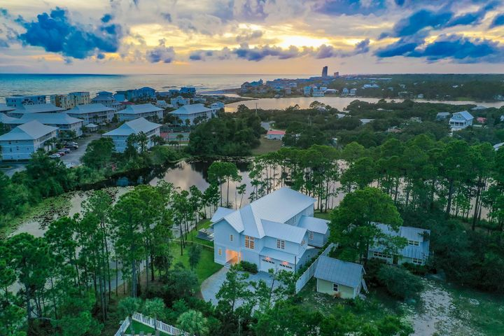 Phenomenal fully furnished 6-bedroom, 6.5-bath lakefront home boasting 4,753 sq ft & 2-car garage located in the heart of 30A with no HOA fees! This home is positioned at the end of the street on Lake Tresca, offering tranquility & the luxury of privacy. Nestled between Eastern Lake & Deer Lake, the home is surrounded by natural beauty & pines. Just a short walk, bike, or golf cart ride away from having your toes in the sugar-white sand along the emerald green & crystal blue waters of the Gulf of Mexico! Walton Dunes Beach Access is just 1/2 a mile away & Eastern Lake Beach Access is only a mile away. Enjoy coastal living with incredible outdoor spaces including the large pool overlooking the lake, hot tub deck, wraparound balcony with gas grill & stunning views, and paver stone courtyard. This home offers stunning finishes including hardwood oak flooring throughout with tile in the bathrooms, Quartz countertops, tongue & groove ceilings, beautiful chandeliers, waterfall edge island, state of the art appliances and vaulted ceilings at the entry and main living area. You truly feel at ease in this home and the flow of the house is well thought out. There are two master suites, two living areas, and majority of the bedrooms have beautiful en-suite bathrooms and walk-in closets with custom shelving and drawers. The attention to detail and pride of ownership is superb. The first level features a spacious living area, kitchenette, master suite, & 3 additional bedrooms each with an en-suite bathrooms. One set of French doors leads out onto the oversized covered deck and pool area, while the other set leads out onto a charming open patio courtyard made with lovely paver stones.  The second level features an open living & dining area, elegant kitchen, generous master suite with en-suite bath, bunk room, full bathroom & a large wrap-around entertainment deck. The covered deck is great for grilling & dining outdoors with plentiful seating to relax in and take in the lake view