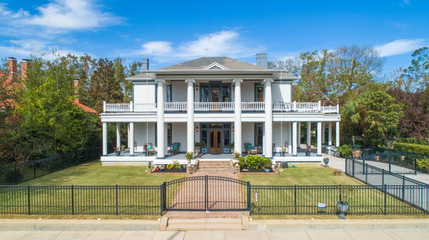 Constructed in 1908 by the Sublett Family, this exquisite Neo-Classical Estate has been fully restored to it's original grandeur with no detail spared. After falling into disrepair and purchased by it's second homeowners in 2004, 4 full bathrooms and a powder room were added as well as a fully renovated kitchen. All porches were reconstructed as well as all new plumbing and wiring installed. This home is perfect for entertaining with a parlor with wet bar, living room, formal dining room with butlers pantry with wet bar and ample outdoor living space on two levels that encompass the home. You'll note the incredible craftsmanship, fully restored wood detail and beautiful hardwood floors and pocket doors as well as 9 fireplaces with original tile work and elegant chandeliers throughout the h Constructed in 1908 by the Sublett Family, this exquisite Neo-Classical Estate has been fully restored to it's original grandeur with no detail spared. After falling into disrepair and purchased by it's second homeowners in 2004, 4 full bathrooms and a powder room were added as well as a fully renovated kitchen. All porches were reconstructed as well as all new plumbing and wiring installed. This home is perfect for entertaining with a parlor with wet bar, living room, formal dining room with butlers pantry with wet bar and ample outdoor living space on two levels that encompass the home. You'll note the incredible craftsmanship, fully restored wood detail and beautiful hardwood floors and pocket doors as well as 9 fireplaces with original tile work and elegant chandeliers throughout the home including an original stained glass window in the dining room. The kitchen is equipped with custom wood cabinetry with pull-out drawers a 5 burner gas cooktop, double wall oven, wet bar, ice maker, trash compactor, 2 drawer dishwasher, pantry and ample cabinet storage. The sizable master suite has his-and-hers walk-in closets, jetted tub with a separate walk-in shower, water closet with an ad