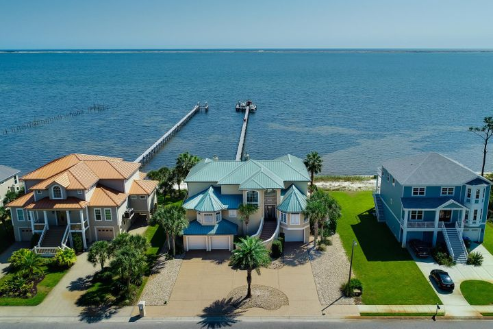 This absolutely stunning 4br/5ba waterfront home in Gulf Breeze has more upgrades and amenities than you can imagine. You'll find views of the Santa Rosa Sound from almost every room, and if that isn't enough, you can walk out of the back door and straight to your own 90ft beachfront. Enjoy the freshly painted interior, an elevator, a man cave with billiard table, 6 bay garage with new doors, high gloss floors, and lighting, new appliances in the indoor and outdoor kitchen, a fully functional home gym, a whole-house vacuum system, and new carpet throughout the entire home. Head outside and find fresh paint on the exterior, a heated pool with new liner, pool bar with remote retractable awning, 8 person hot tub and spa, and a 300' dock with Tiki bar