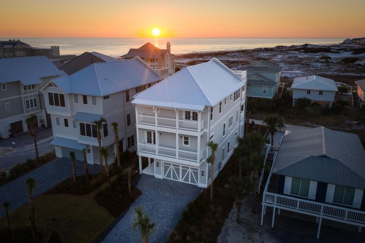 """Under Contract- But taking back up offers! Located in #1 ranked Grayton Beach in a gorgeous location where the sand dunes & crystal-clear gulf water dominate your everyday views.  So many activities to enjoy here- SUP on Western Lake, short walk to the beach and stroll to newly rebuilt Red Bar for dinner! This custom masterpiece home is sure to impress even the most discerning buyer. Coastal finishes woven with transitional clean lines make this home so visually pleasing and relaxing. 1st floor features a great entry way where the beautiful herringbone pattern floor tile is showcased. There's a guest room on this ground level that is large enough for a king bed and also a laundry room fully equipped with 2 sets of washer and dryers and cabinets for storage. Out the back door is your outdoor oasis with fully equipped outdoor kitchen and inset pool with bench seating to just relax and take in the sound of the waves crashing.  Take the elevator or stairs to the 2nd floor and you'll find 3 more bedrooms including a luxurious owners suite with a wall of glass to take in the views outside off the covered porch.  Owner's bath is sure to wow with dramatic 24 x 48 sheets of calcatta porcelain tile on the floors and arabesque decorative tile around free-standing tub wall with large white, glossy subway tile in separate shower.  Just down the hall there's a bunk room with 3 sets of bunks & attached bath with triple sinks!  The tile & lighting here is whimsical and fun= perfect for a bunk room!  There's another bedroom suite on this floor and wet bar in the hall for easy access to a cup of coffee in the morning or a night cap before bed on the 367 sq ft porch. The 3rd floor offers beautiful views everywhere.  The soaring, vaulted ceiling with ship lap brings a coastal, airy feel to this space.  Kitchen is built for a chef with all sub zero appliances including a 60"""" gas range with double oven, drawer microwave, and TWO 30"""" glass front refrigerators with freezer on bottom.  Wet """
