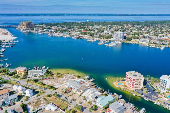 This 3 bedroom, 3 bath, Plus Extra Bunk Room (or Nice office Space) is sitting in a Spectacular Waterfront Location on the Destin Harbor! Conveniently located in the Heart of Destin on Holiday Isle. This Multi-Level Townhome is Perfect for Living your Dream on the Water, Use as a Vacation Home, or a Phenomenal Rental Income Machine doing over 90k a year in Short Term Rent! Dock your boat right in your backyard in your own private boat slip, hop on and you are less than 10 minutes to Destins East Pass, the Gulf of Mexico and Crab Island! In Season, Destin Water Taxi can pick you up at your back dock and deliver you to all of the Harbors Waterfront Restaurants/Bars and HarborWalk Village! Currently being used as a Vacation Rental sleeping 10 people. 1 King, 2 Queens, 2 Singles & 2 Bunkbeds. Several Upgrades Completed in 2019 to Include a New HVAC install. New Vinyl Wood Flooring throughout the Living area, Stairs and Bedrooms. The Top Floor Guest bathroom has a beautiful high-end new Vanity and Mirrors. New Ceiling fans throughout, Fresh paint in 2019, and All New Furnishings.  The Kitchen has beautiful granite countertops, Stainless Appliances including a Brand New Refrigerator in 2019. Bottom Level includes a Spacious Garage and a Huge Master Suite with Separate Shower, Whirlpool/Jacuzzi Tub and double vanities. Bedroom is overlooking the canal and has its own private deck for sitting out and watching the boats go by. Waterfront is getting harder and harder to find, don't let this one slip by! Enjoy all the Harbor has to offer, Boating, restaurants, nightlife, Weekly Fireworks show in the season AND This Gem is only a couple blocks walk to the Public Beach Access! Have your toes in the Sand and viewing the Most Gorgeous Emerald Waters Destin is known for in minutes!  2232 SF under roof per plans but the county records show 2154 SF *Buyer is Responsible for Personally verifying all dimensions and details about this property. Any information contained in this listing 