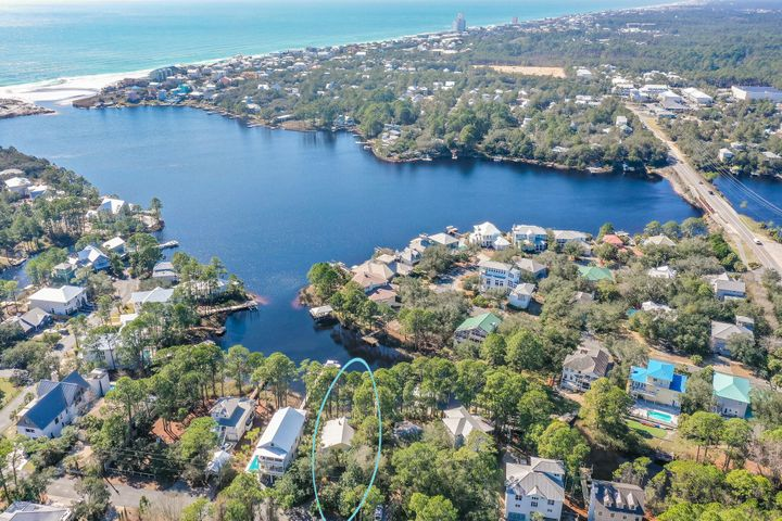 Located south of 30A on the Eastern Lake nestled among mature landscaping this home boasts 2,592 square feet of heated/cooled area and 3,724 total area. Here is your opportunity to own on the lake! Main level L-shaped wooden deck is perfect for watching the sunset. Kitchen, living and bedroom and bath on main level. Huge master bedroom with en-suite master bath on 2nd level.. At the top of stairs is an open area loft that could  be made into  additional bedrooms. Hurricane impact Anderson windows, 2 x 6 construction, a wood burning stove, this home has some history.. Security system. separate storage room & parking on ground level with walkway out to your dock on the lake.  Additional pictures coming soon.