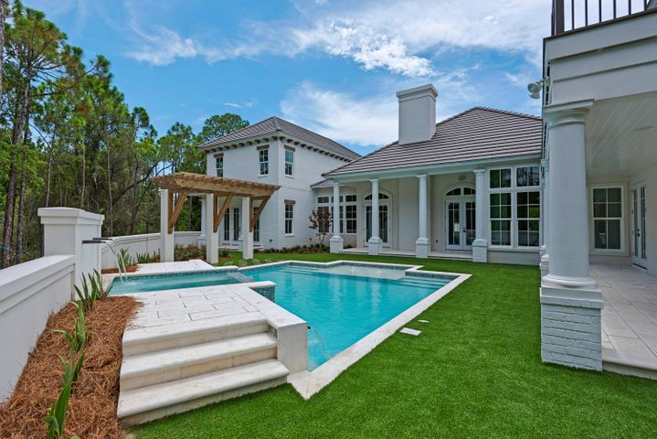 This beautiful 4,432 sq. ft. home in the gated community of Regatta Bay is a true masterpiece. The front courtyard opens to 3 sets of solid mahogany entry doors, and a gallery of archways greets you in the foyer. Custom details throughout the home include pecky cypress and coffered ceilings, a limestone fireplace, handmade cabinetry, and much more. The great room, office, impeccable kitchen and luxurious master suite are located on the first floor. Take the stairs or elevator to the two guest suites and a second kitchen and living room, as well as an outdoor kitchen and large patio on the second floor. The first floor patio is perfect for entertaining by the pool, featuring several fountains. Situated on 1.21 acres and backing up to nature preserve, this home offers incredible privacy.